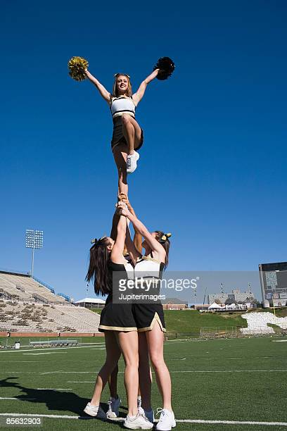 cheerleaders performing stunt - asian cheerleaders stock photos and pictures