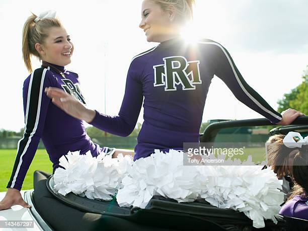 cheerleaders riding in car - candid cheerleaders stock photos and pictures