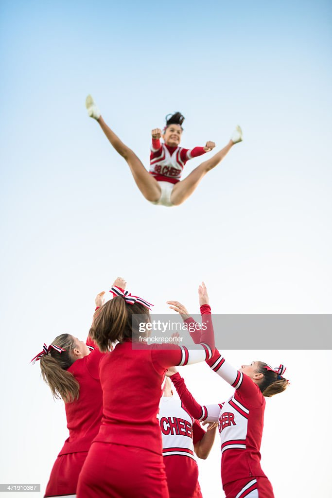 Cheerleaders throw up a girl in the air : Stock Photo