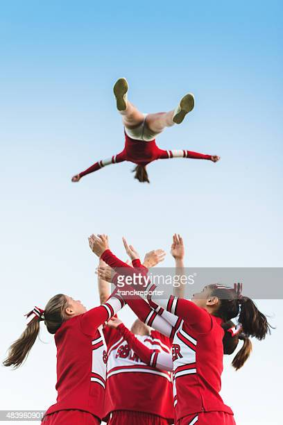 cheerleaders throw up a girl in the air - cheerleaders stock photos and pictures