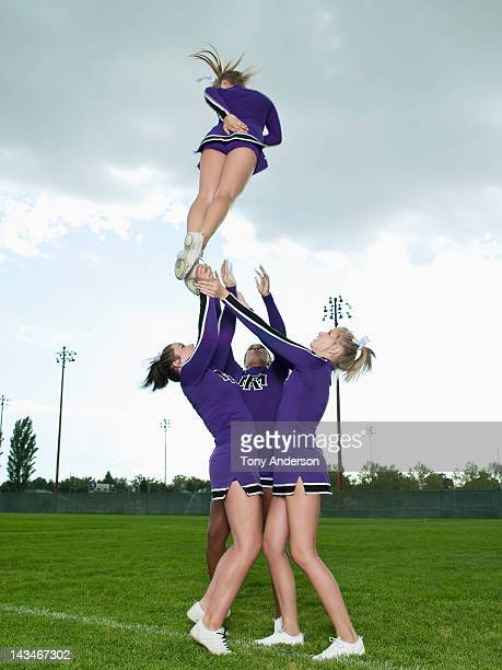 cheerleaders throwing girl into the air - candid cheerleaders stock photos and pictures