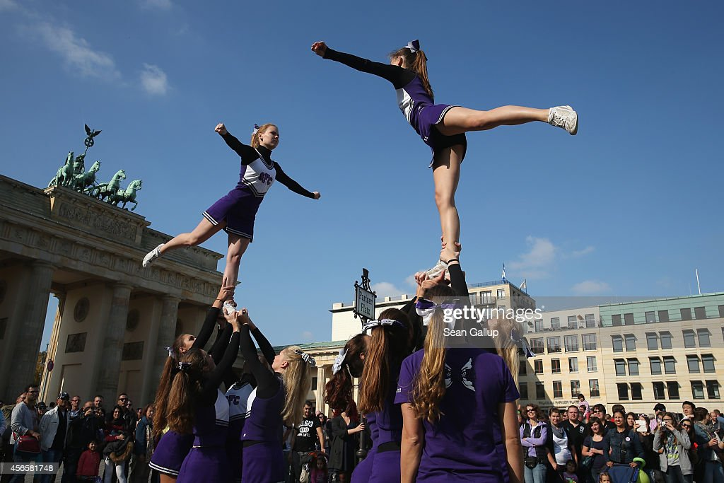 A cheerleading squad from the Spirit Ferries Chearleaders perform near the Brandenburg Gate on German Unity Day (Tag der Deutschen Einheit) on October 3, 2014 in Berlin, Germany. Germany is celebrating the 24th anniversary of the day when former West Germany and East Germany reunited into modern Germany in 1990 following the end of the Cold War. This year Germany will also celebrate the 25th anniversary of the fall of the Berlin Wall that heralded the collapse of communist authority in East Germany.