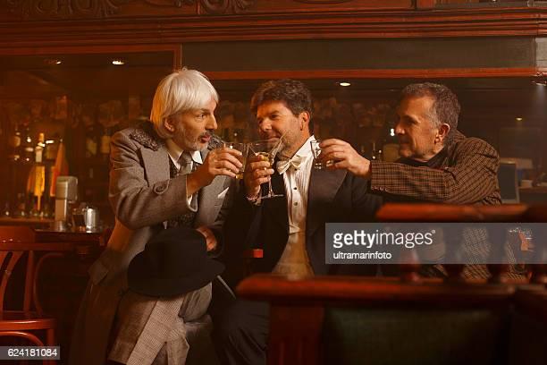 Cheers Retro pub celebration  Senior men  drinking whiskey and martini
