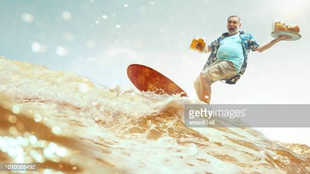 brinde! conceito de férias. retrato de estúdio de belo homem sênior com barba grisalha e chapéu segurando a garrafa de cerveja - taking a shot sport - fotografias e filmes do acervo