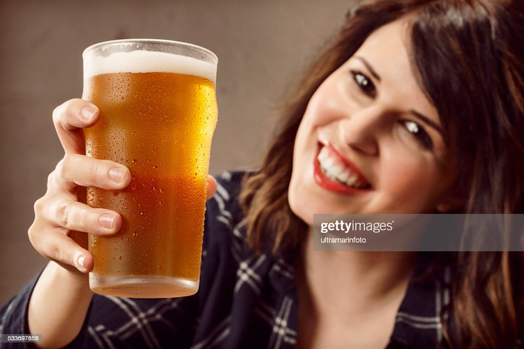 Cheers Giovane donna seduta in un bar e bere birra : Foto stock