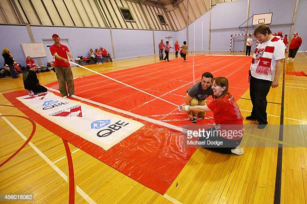 Cheersquad members apply pieces of tape to the banner during the creation of the Sydney Swans AFL banner at Glenroy College on September 24 2014 in...