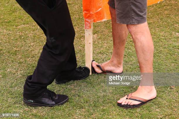 GWS cheersquad members keep the banner still with their feet during the round three AFLW match between the Collingwood Magpies and the Greater...