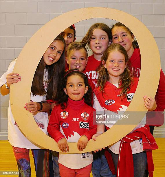 Cheersquad members pose with a letter stencil during the creation of the Sydney Swans AFL banner at Glenroy College on September 24 2014 in Melbourne...