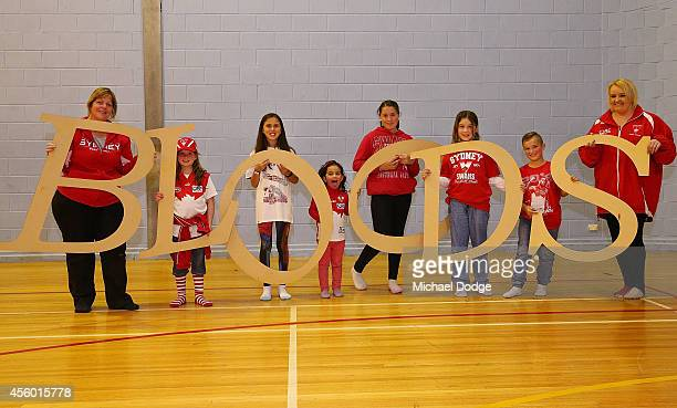 Cheersquad members pose with letter stencils during the creation of the Sydney Swans AFL banner at Glenroy College on September 24 2014 in Melbourne...
