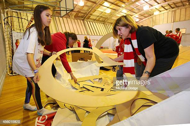 Cheersquad members sort out letter stencils during the creation of the Sydney Swans AFL banner at Glenroy College on September 24 2014 in Melbourne...