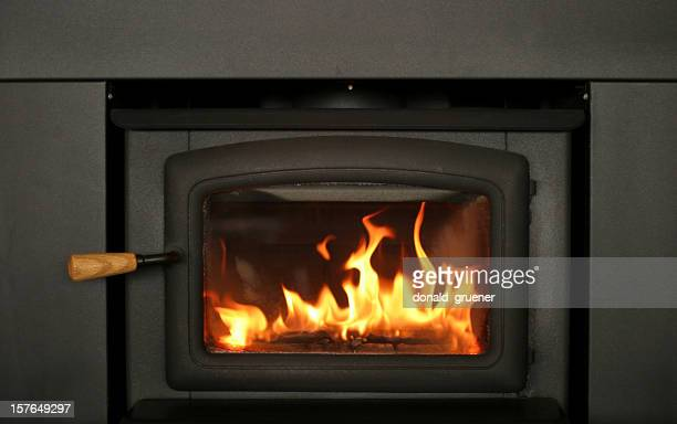 cheery fire burning in fireplace insert - inserting stock pictures, royalty-free photos & images