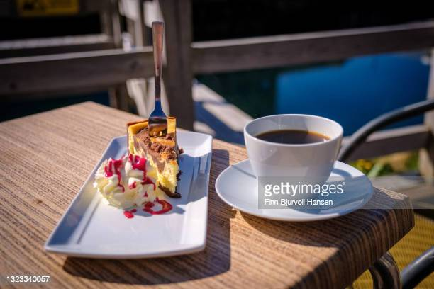 cheescake with choclate and cream coverd with strawberry cyrup and a cup of coffee - finn bjurvoll stock pictures, royalty-free photos & images