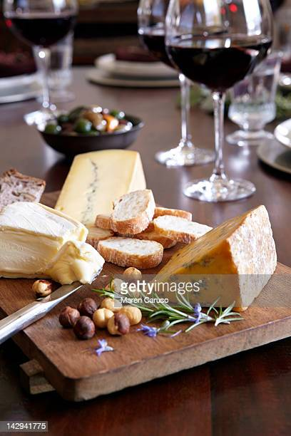 Cheese and bread dish, wine, olives, on table