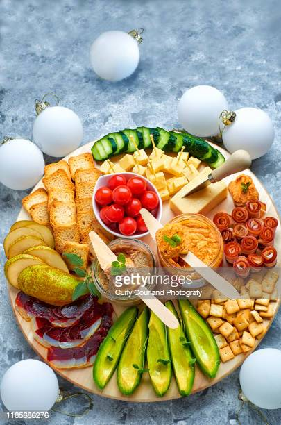 cheese and charcuterie board with cheddar cheese, avocado, bacon, duck prosciutto, cherry tomatoes, crispbreads, crackers, cucumber, goose rillettes, pear, hummus and herbs. christmas and new year decoration. ideal for party or picnic - nieuwjaarsreceptie stockfoto's en -beelden