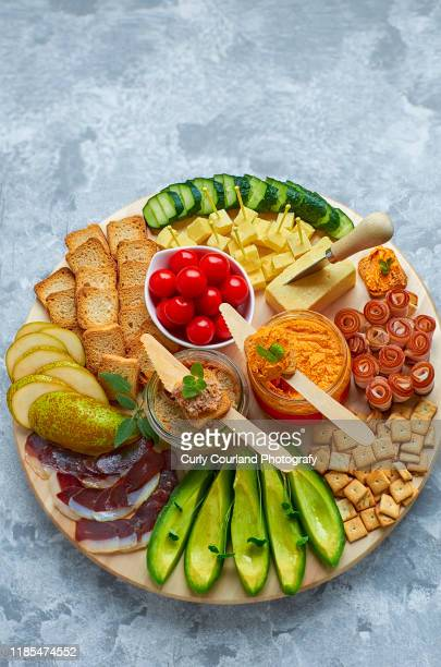 cheese and charcuterie board with cheddar cheese, avocado, duck breast, bacon, cucumber, cherry tomatoes, pear, crispbread, goose pate, hummus with sundried tomatoes, crackers.ideal for party. - charcuteria fotografías e imágenes de stock