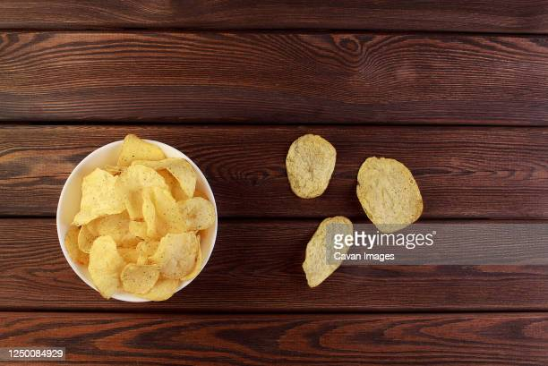 cheese and chive potato crisp snack in brown bowl on wooden background top view - bowl stock pictures, royalty-free photos & images