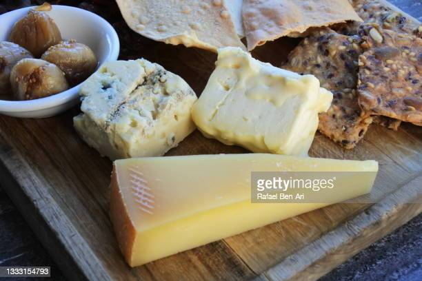 cheese and crackers on a wooden serving board close up - rafael ben ari fotografías e imágenes de stock