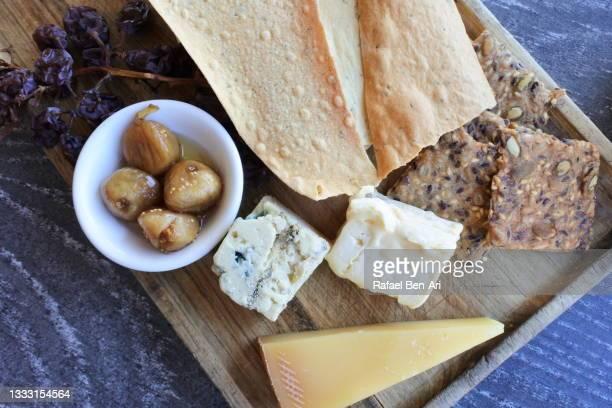cheese and crackers on a wooden serving board - rafael ben ari fotografías e imágenes de stock
