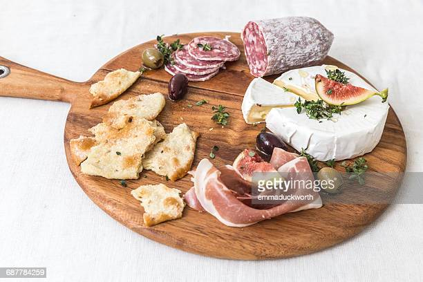 cheese and cured meats on chopping board - charcuteria fotografías e imágenes de stock