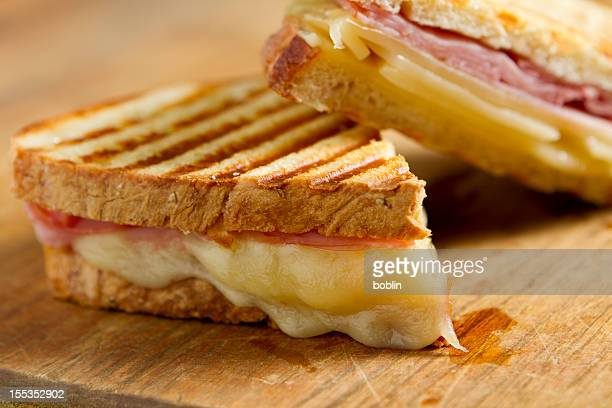 Cheese and ham panini sandwiches on a wooden board