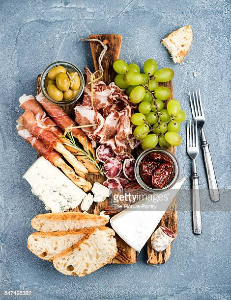 Cheese and meat appetizer selection or snack set for wine. Prosciutto di Parma, salami, bread sticks, baguette slices, olives, sun-dried tomatoes, grapes on rustic wooden board over grey concrete backdrop