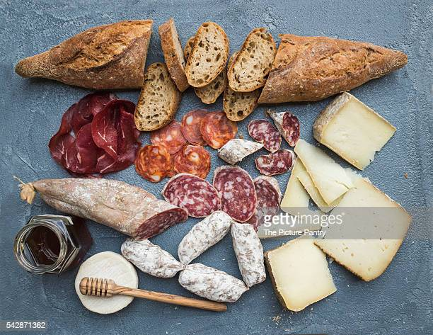 Cheese and meat appetizer selection or wine snack set. Variety of italian cheese, salami, bresaola, baguette, honey on over grey-blue concrete backdrop, top view.