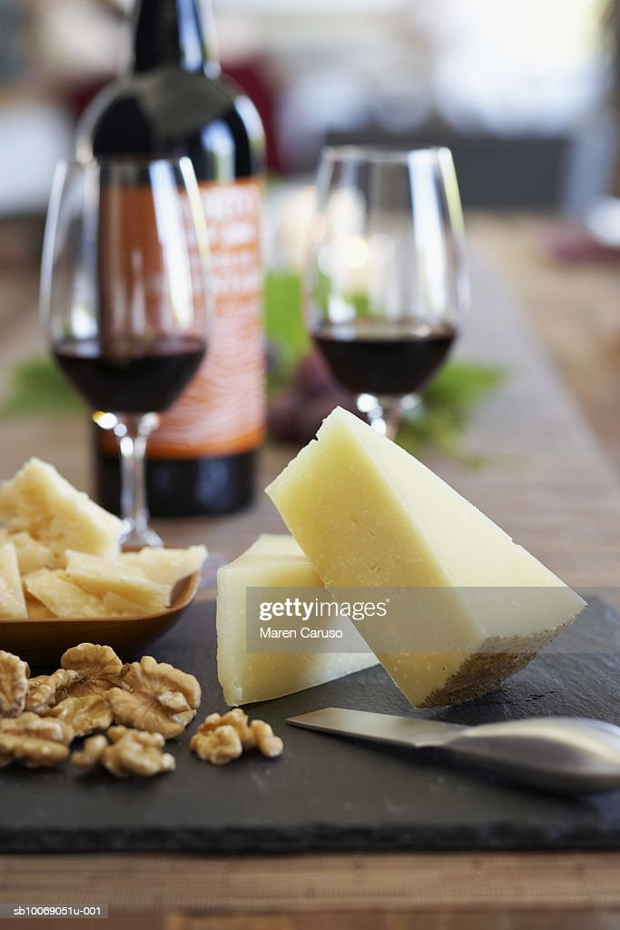 Cheese and nuts on cutting board, wine glasses in background, close-up : Stockfoto