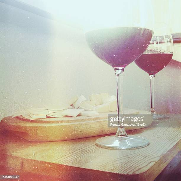 Cheese And Red Wineglasses On Table