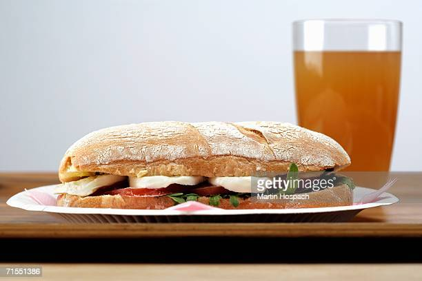 Cheese and salad ciabatta next to glass of ice tea