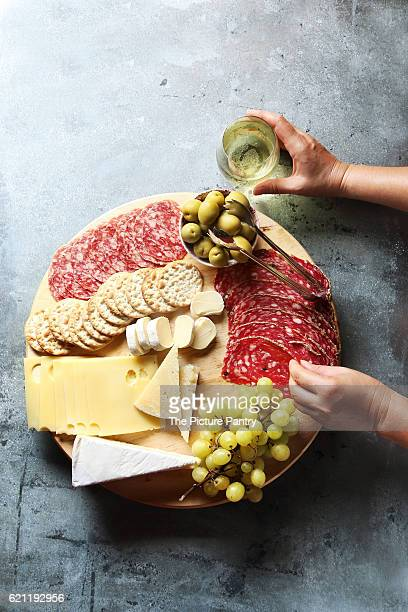 Cheese board with assorted sausages and salami, fresh fruit and various cheeses.Female hand reaching salami from a platter.