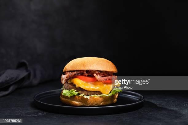 de hamburger van de kaas met bacon op zwarte donkere achtergrond - burger menselijke rol stockfoto's en -beelden