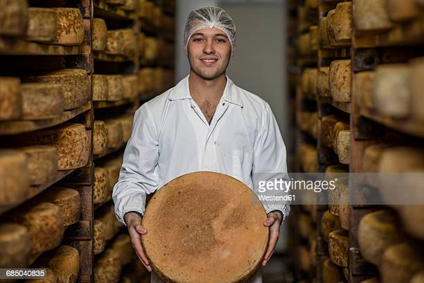 Cheese factory worker proudly holding loaf of cheese