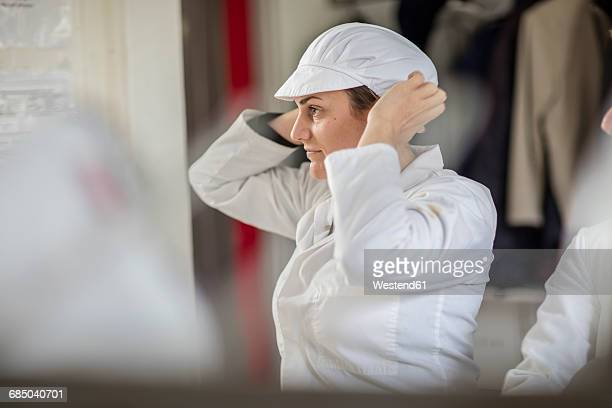 Cheese factory worker putting on protective clothes