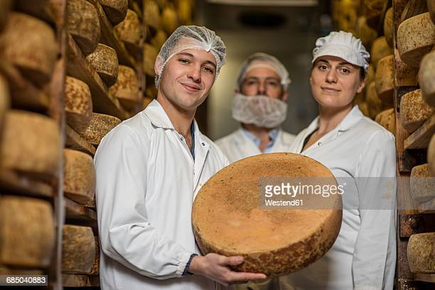 Cheese factory workers proudly holding loaf of cheese