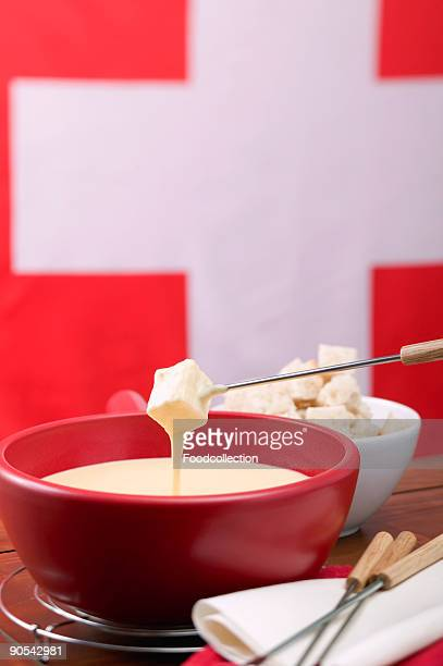 Cheese fondue in front of Swiss flag, close up