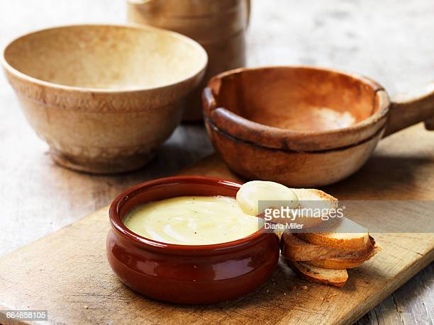 Cheese fondue in terracotta bowl