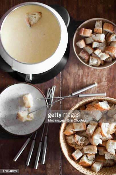 Ein Käsefondue auf den Tisch. Kantenlänge Brot und lange