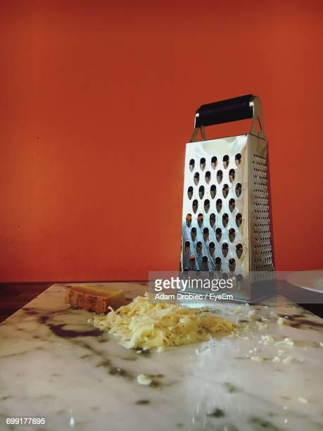 Cheese Grater On Marble At Table Against Orange Wall