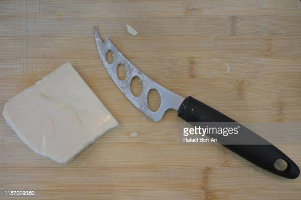 cheese knife and cheese slice on a wooden cutting board - rafael ben ari stockfoto's en -beelden