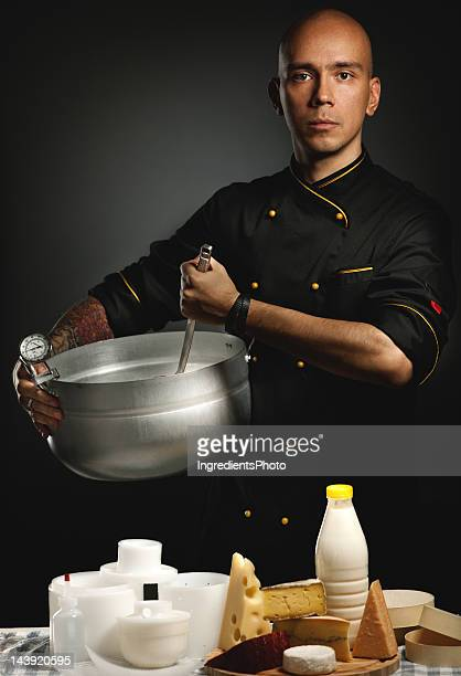 Cheese maker in black chef coat holding a silver pan.