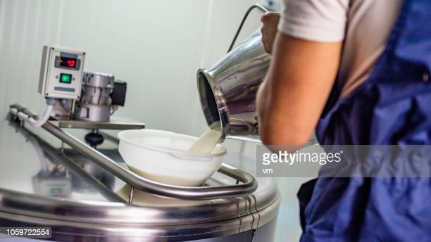 cheese maker pouring milk into a stainless steel heating element - fermenting stock pictures, royalty-free photos & images