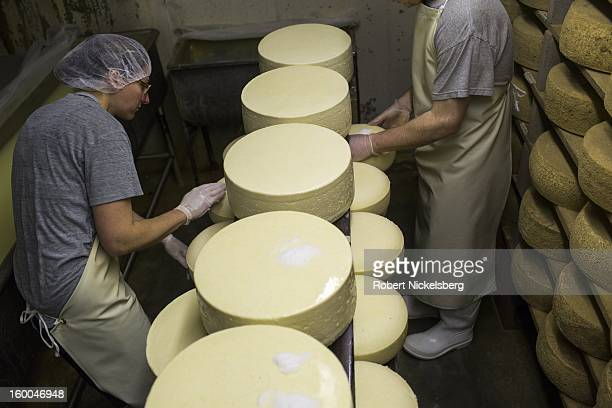 Cheese makers Becky Smith left and Pat Spranzo right at the Cato Corner Farm salt the rind of newly made wheels of cheese January 10 2013 in the...