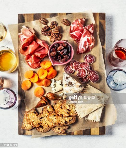 cheese plate assortment of french cheese served with walnuts, dried fruit, salami and prosciutto on a wooden cutting board on white background - cuisine française photos et images de collection