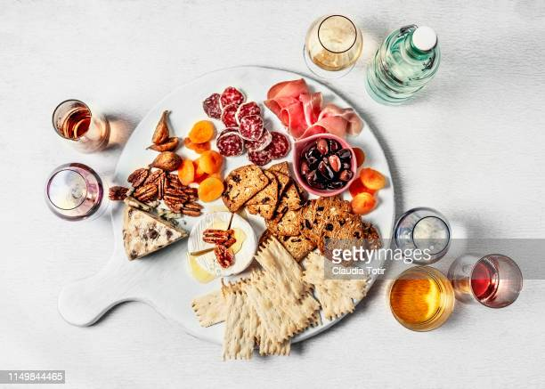cheese plate assortment of french cheese served with walnuts, dried fruit, salami and prosciutto on a cutting board on white background - hartig voedsel stockfoto's en -beelden