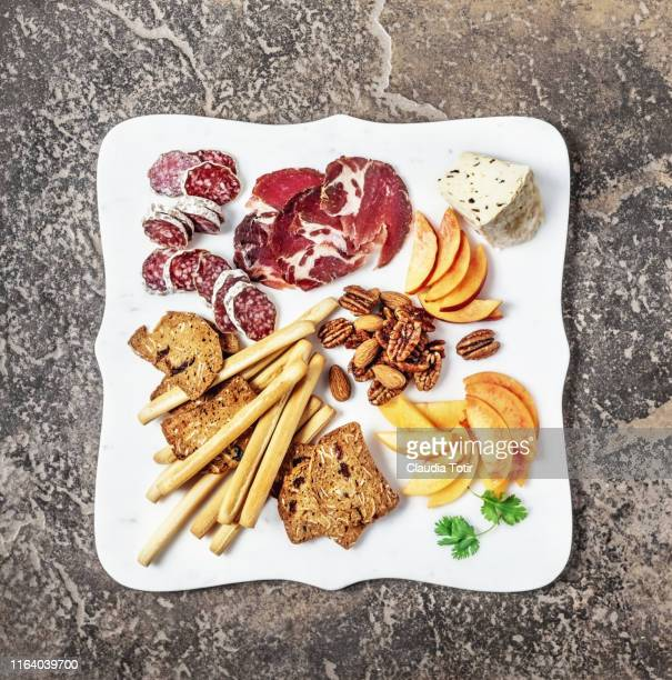 cheese plate assortment of french cheese served with walnuts, salami, bread sticks, and crackers on a white cutting board on rusty, stone background - salumeria stock photos and pictures