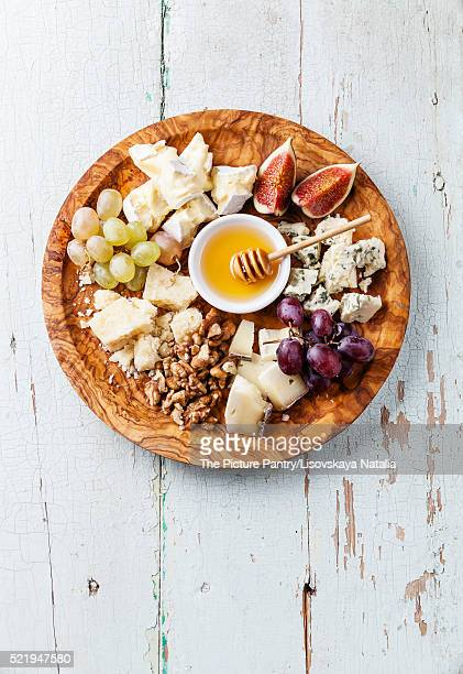 Cheese plate Assortment of various types of cheese on olive wood