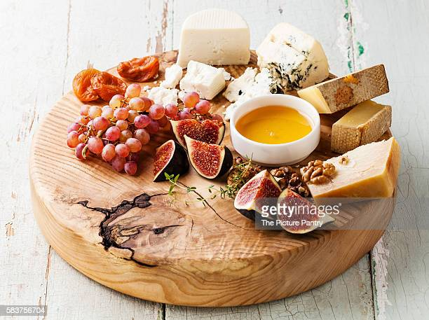 Cheese plate Snacks assortment with honey on white plate