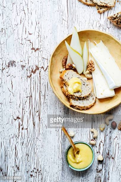 cheese platter. brie cheese, bread, nuts,  and honey - brie stockfoto's en -beelden