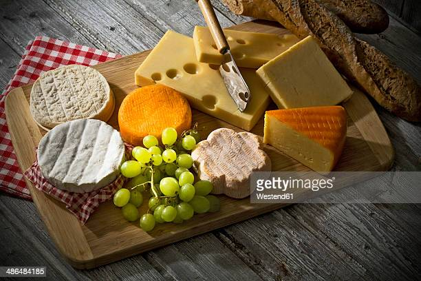 Cheese platter, different cheese, french cheddar, french soft cheese, french sheep cheese, camembert, emmentaler, and austrian mountain cheese and wholemeat baguette on wooden board