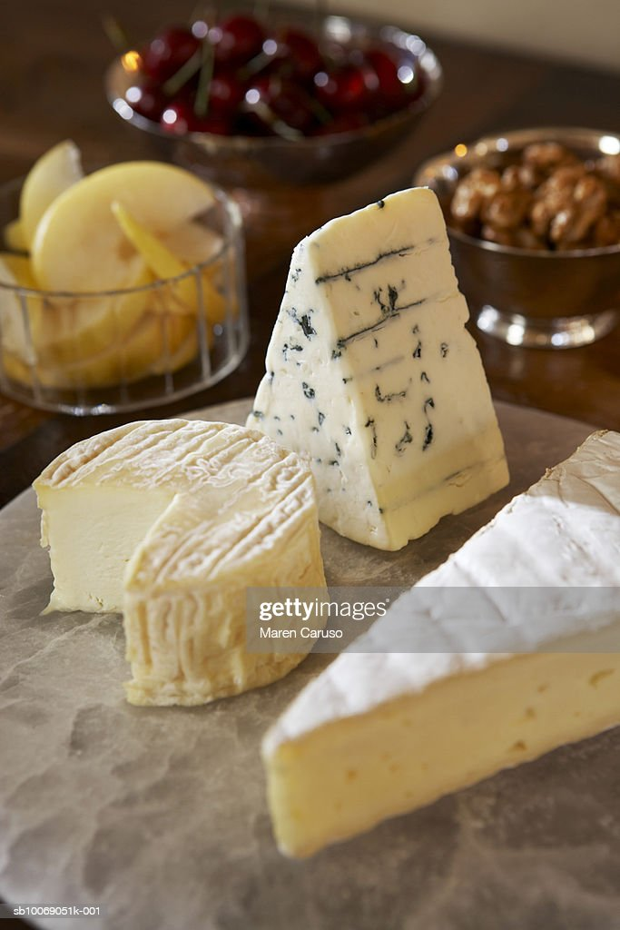 Cheese slices on cutting board, bowls of nuts, cherries and pears in background, close-up : Stockfoto